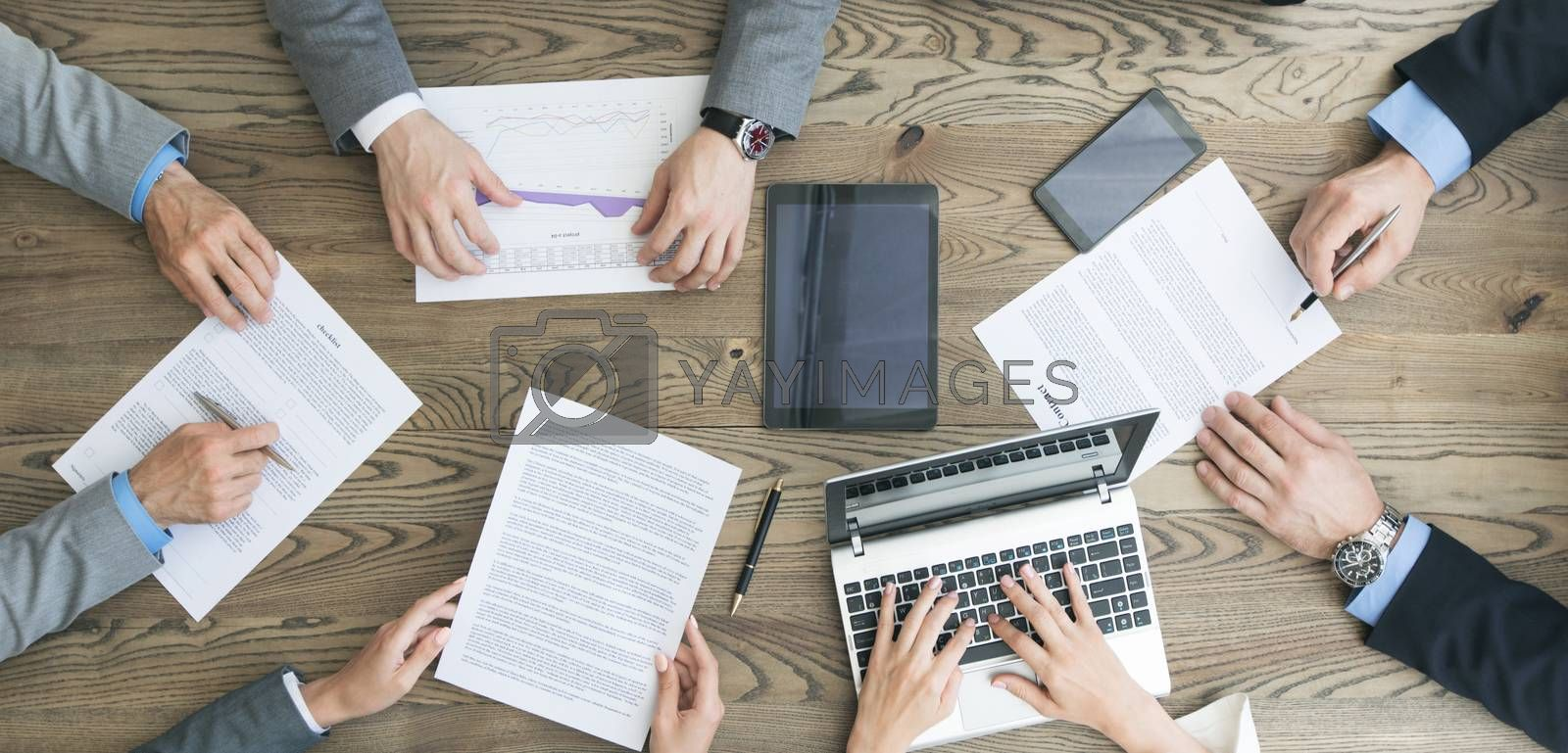 Business team working with contract, financial reports and laptop dicussing deal sitting around office table