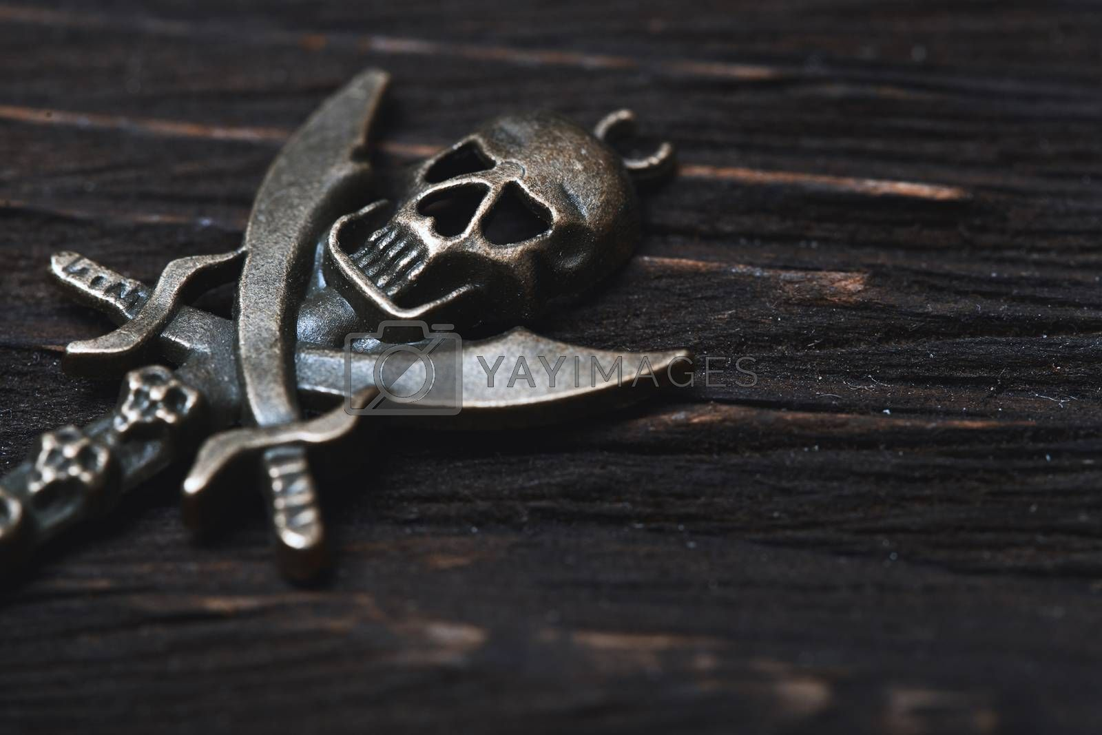 Vintage skull and pirate key on a wooden table. Close-up view