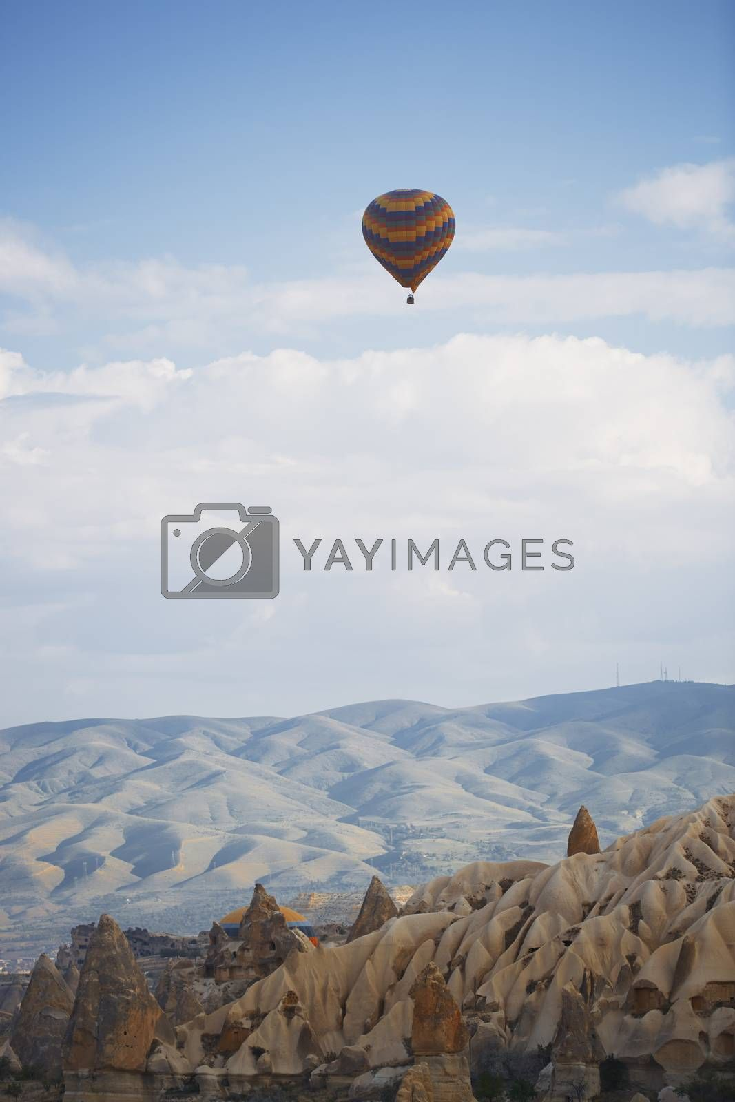 Hot air balloon flying over the rocky land by Novic