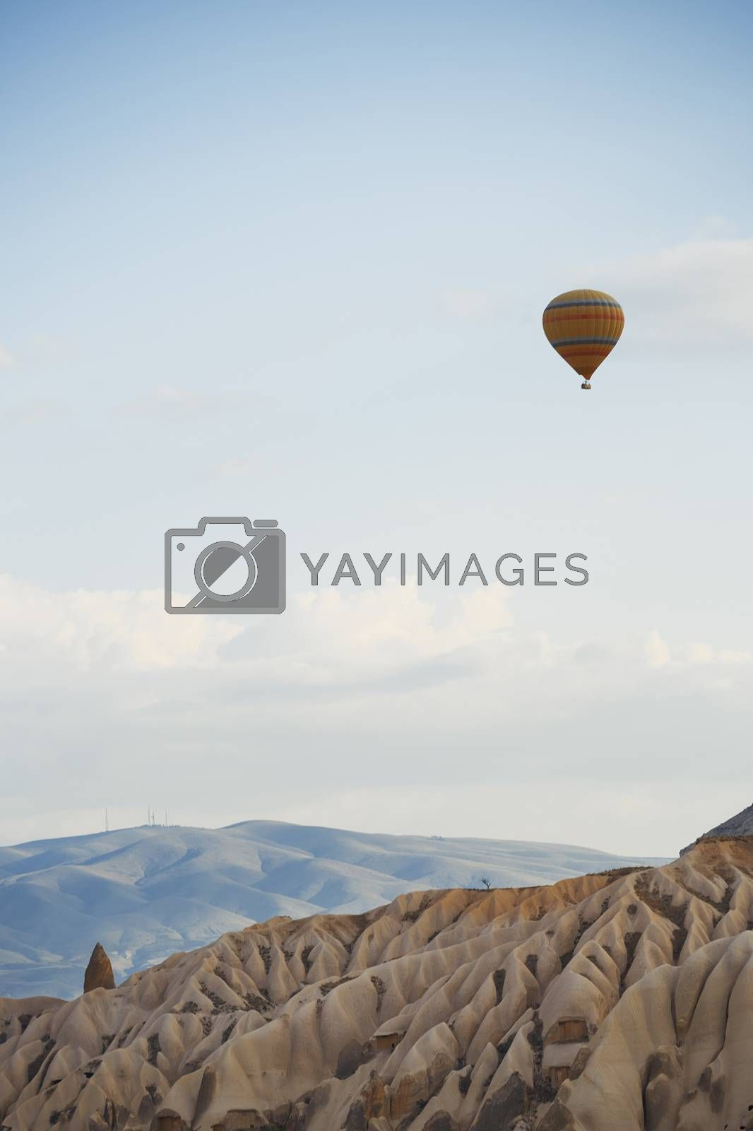 Hot air balloon flying over the rocky land. Cappadocia, Turkey