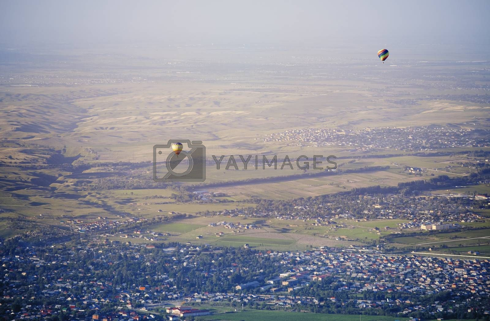 Hot air balloons above the green field and villages