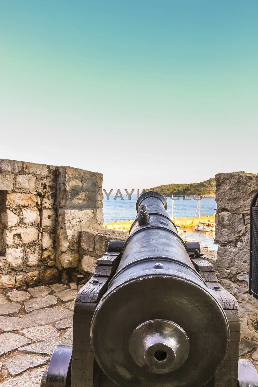 Aiming view of a cannon on the fortress of Dubrovnik City Walls with parts of Lokrum Island in the background
