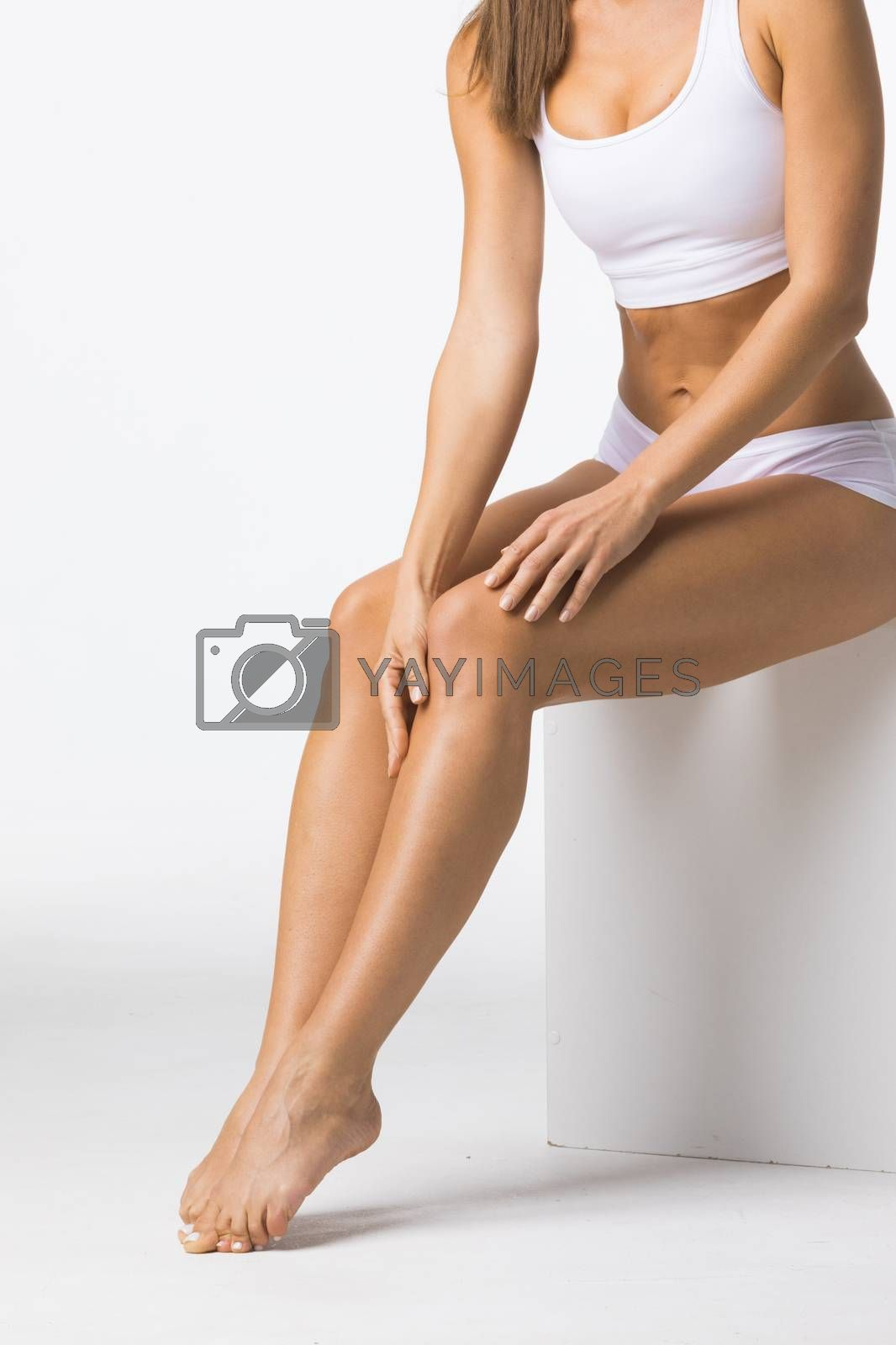 Young beautiful woman in white cotton underwear sitting and touching legs