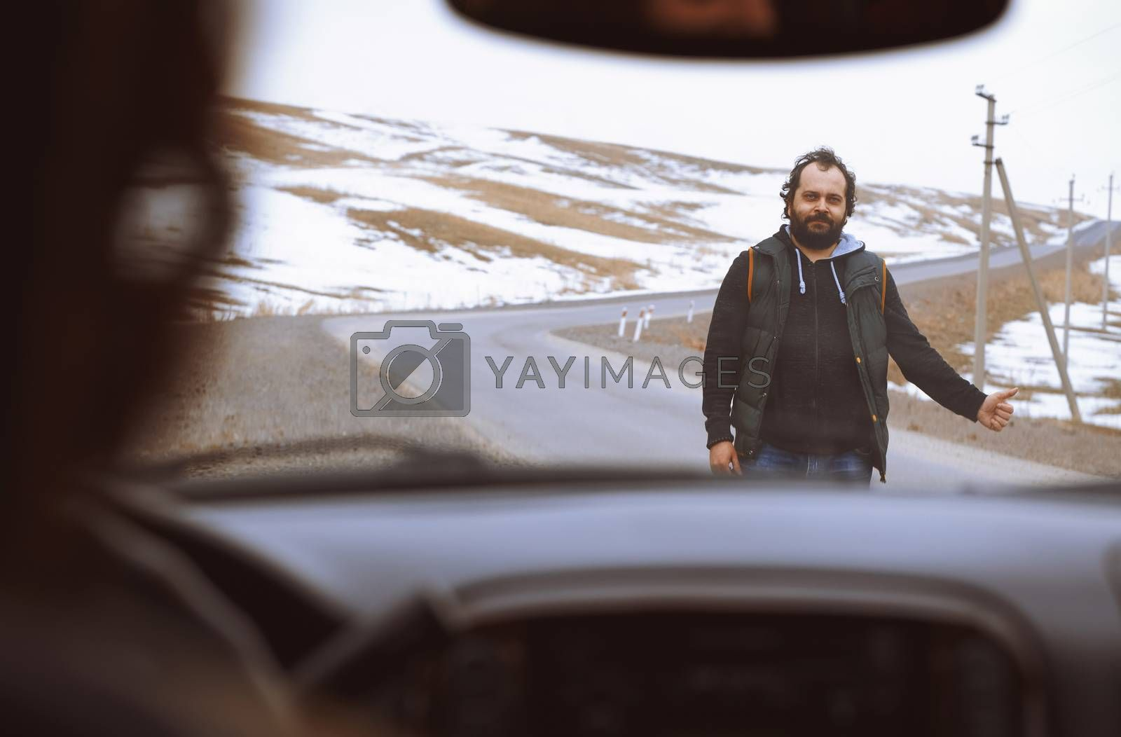 Traveller on the rural road trying to stop a car for assistance by Novic