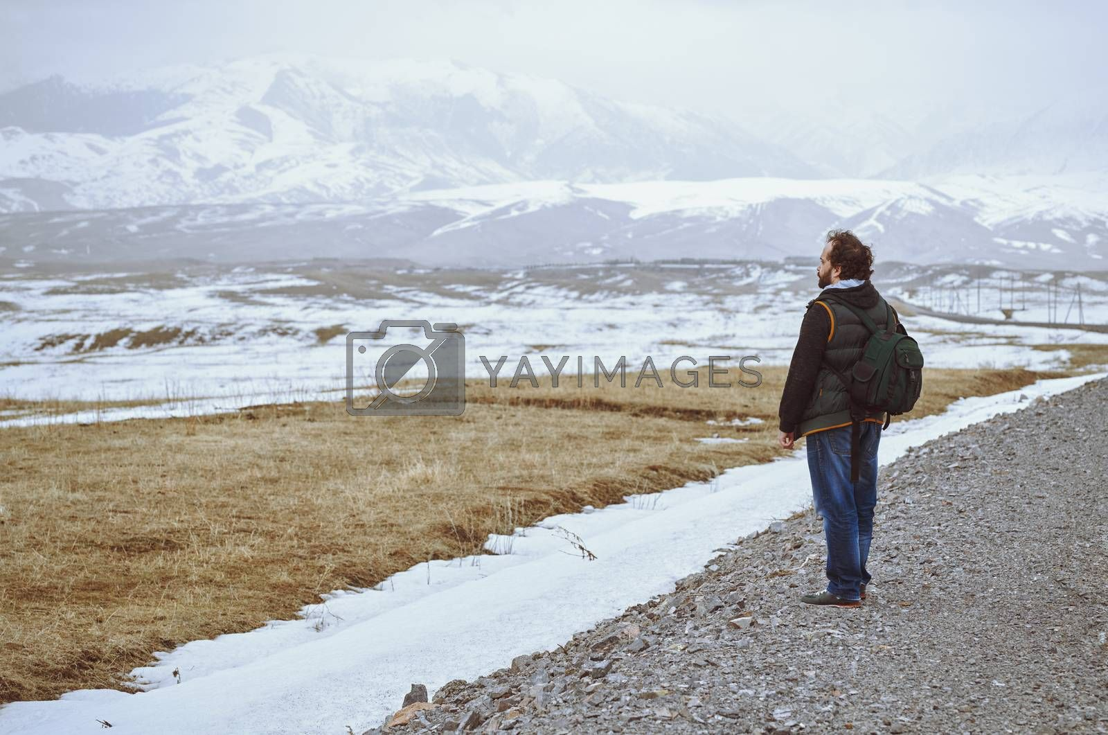Touris wearing backpack and standing at the rural road while looking at the winter mountains