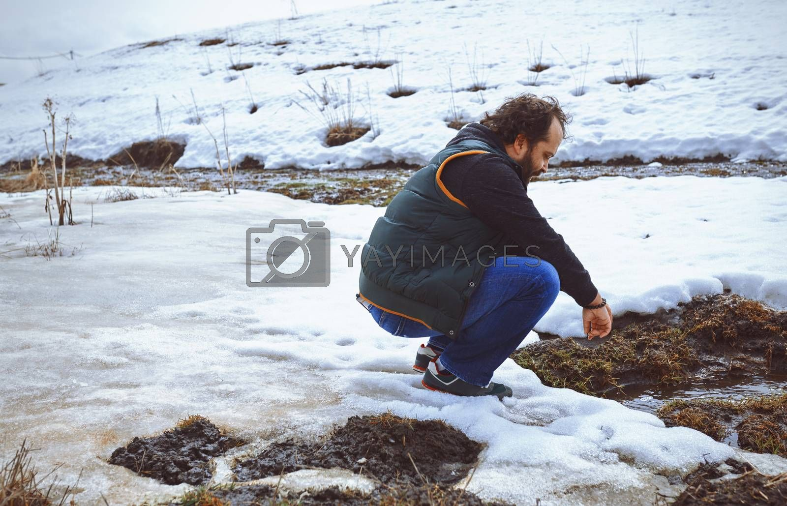 Traveller squatting at the snowy marsh