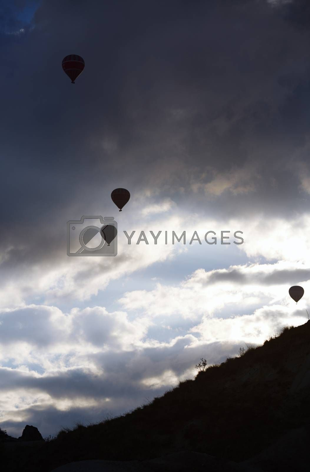 Silhouettes of the hot air balloons flying over the mountain