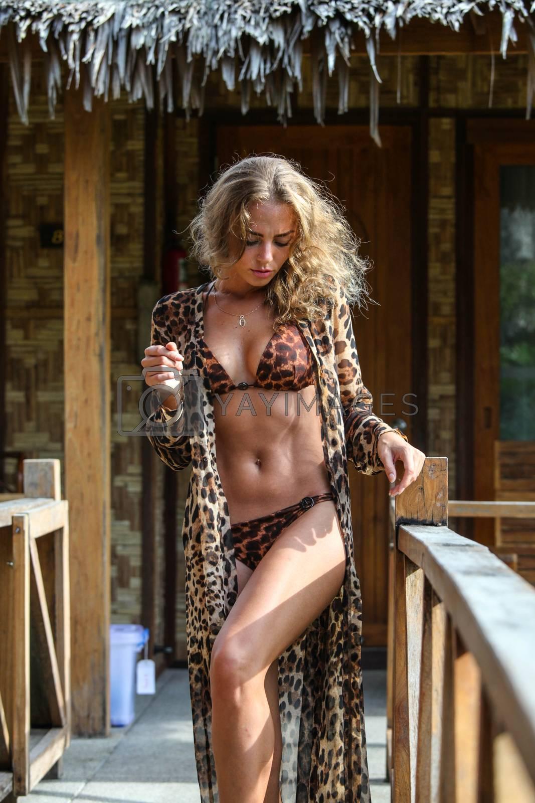 Stylish fashionable woman posing near house in tropical resort