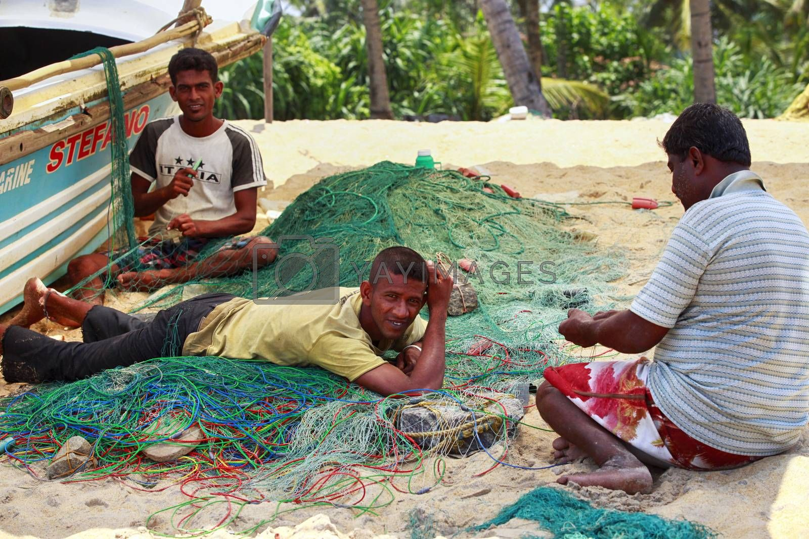 Kalutara, Sri Lanka - April 10, 2011: Three fishermen with fishing nets on the beach of Kalutara in Sri Lanka.