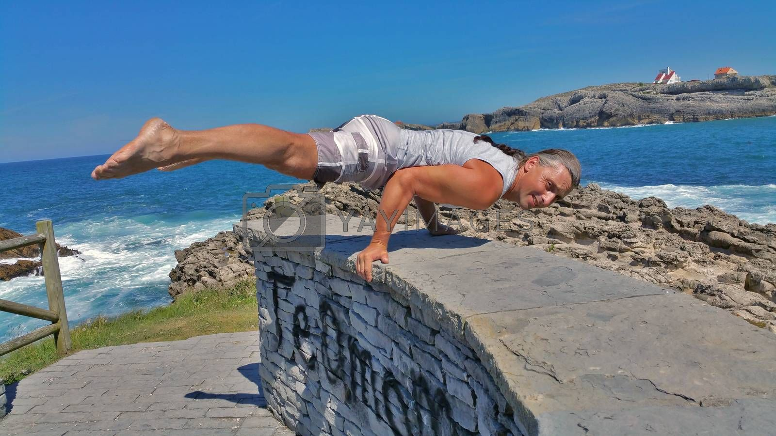 man in white shorts and white t-shirt does gymnastic exercise on a stone wall against a blue sea by zakob337
