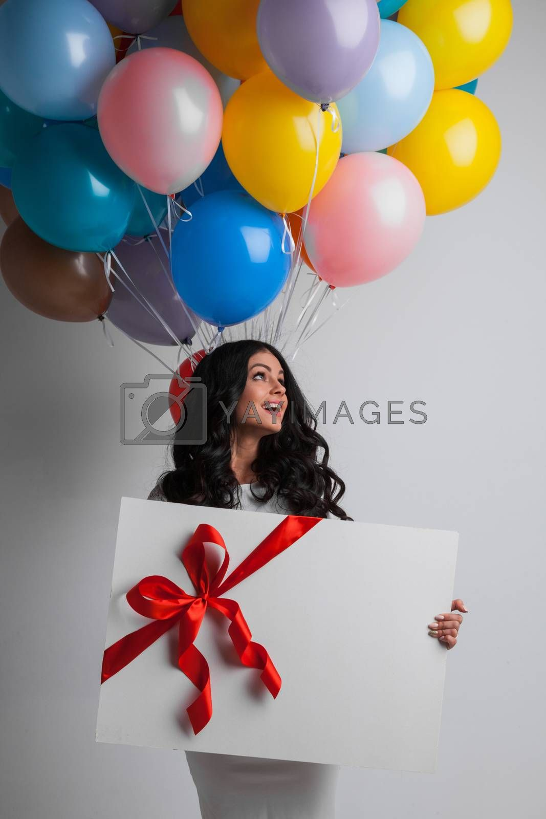 Young pretty woman with colored balloons and gift with ribbon bow or big greeting card