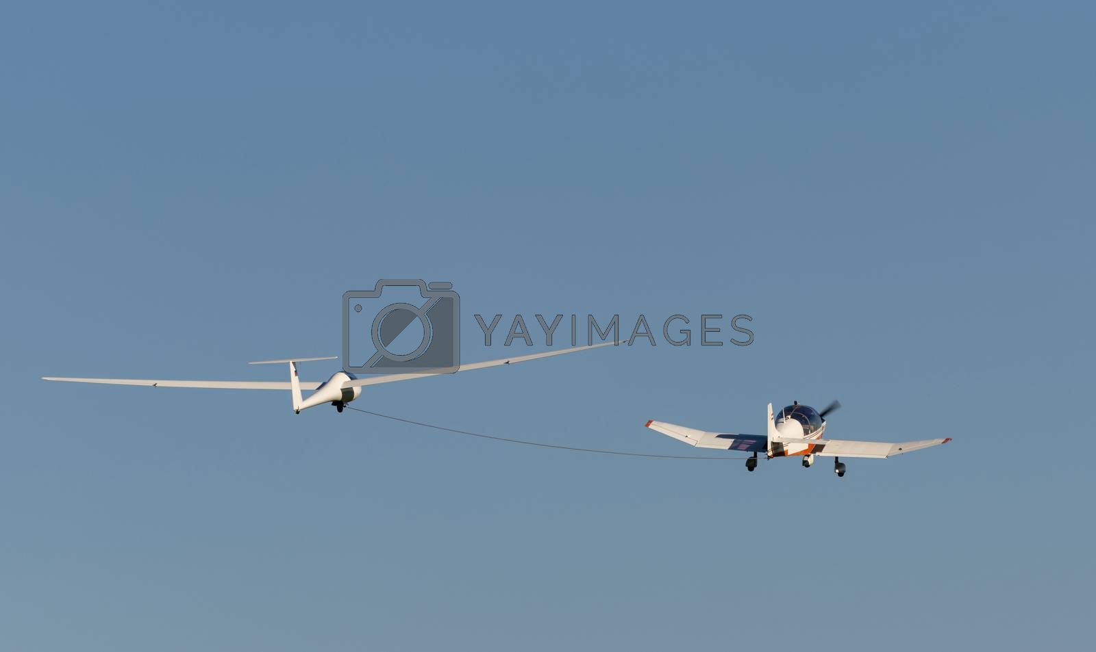 White modern glider which is increased by a small motorized sport airplane