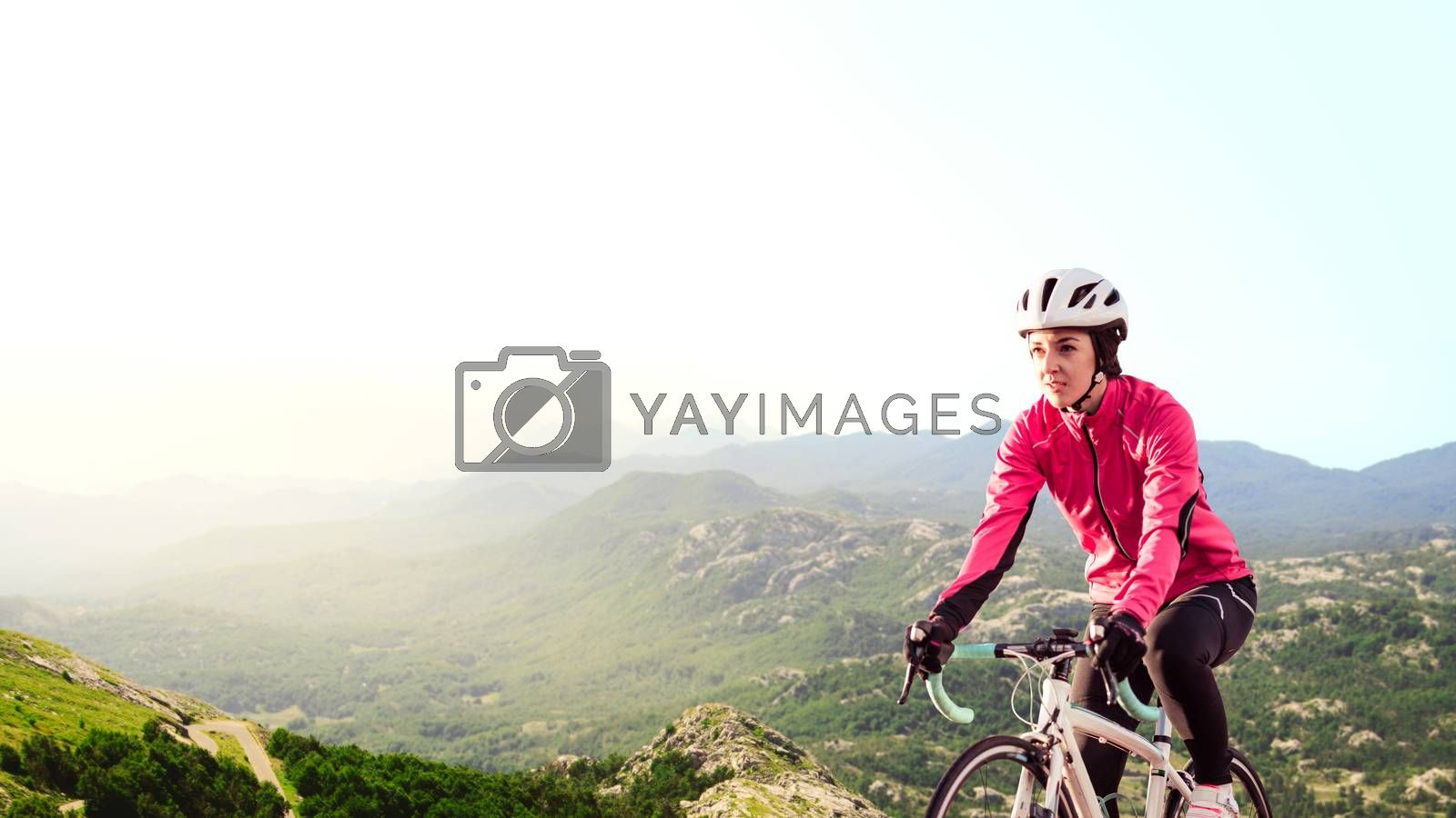 Young Woman in Bright Pink Jacket Riding Road Bicycle on the Mountain Alpine Road. Healthy Lifestyle and Adventure Concept.