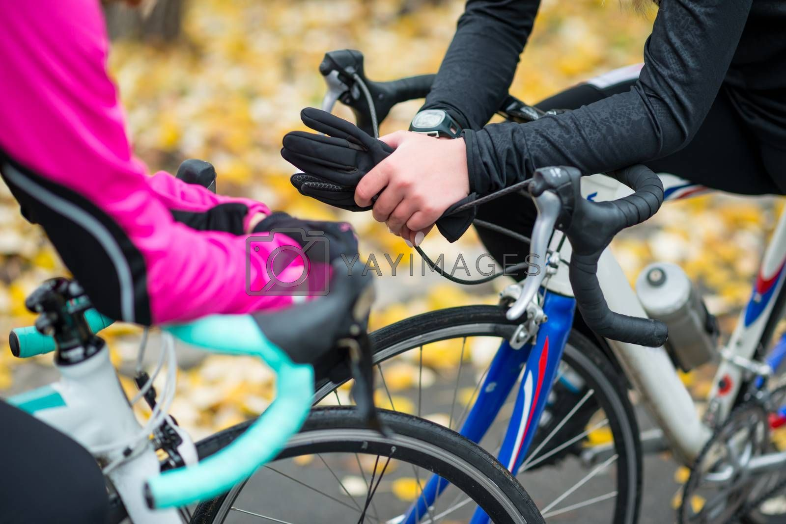 Two Young Female Cyclists with Road Bicycles Resting in the Park in Cold Autumn Day. Healthy Lifestyle. by maxpro