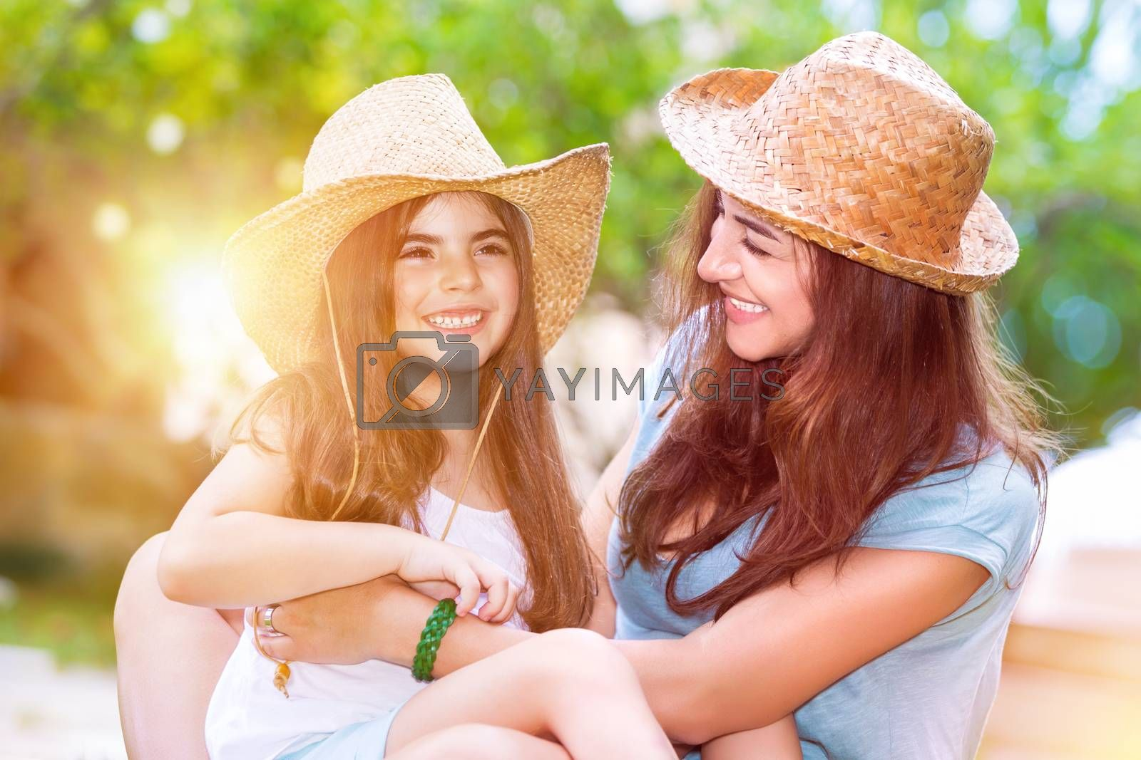 Portrait of a joyful young mother with a cute cheerful daughter wearing same straw hats and playing outdoors, laughing and having fun, portrait of a happy family enjoying life
