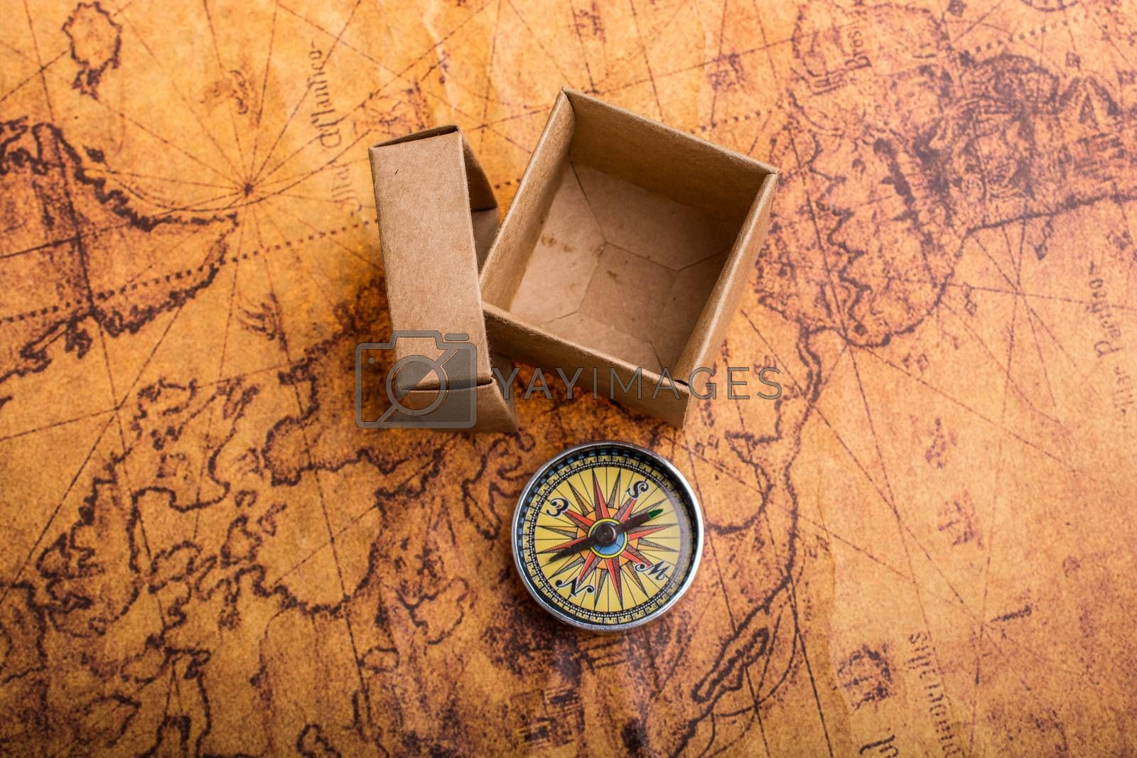 Compass on old map beside a box as a concept of traveling