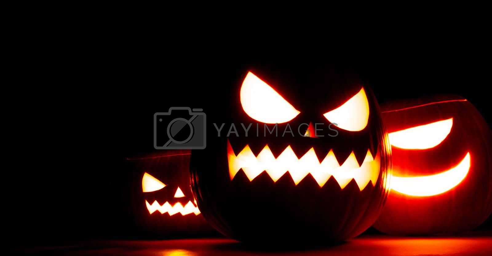 Group of Halloween pumpkin heads jack o lantern in darkness