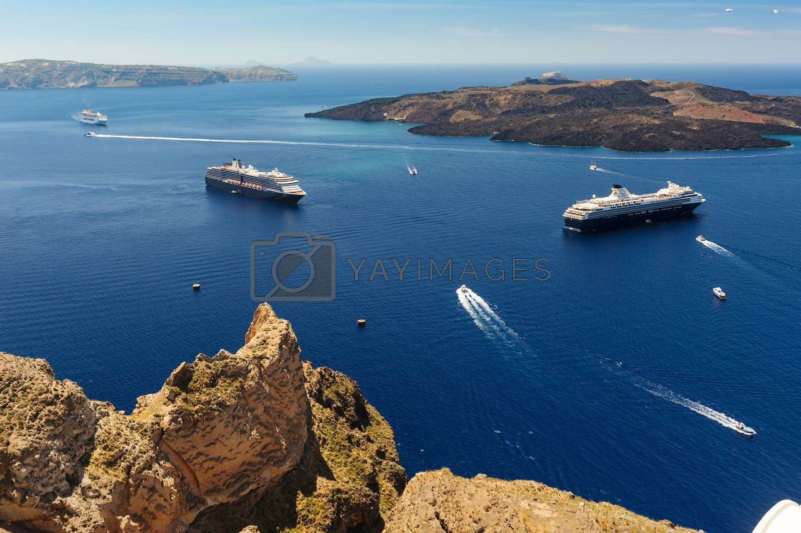 Typical view from Fira village to caldera sea with cruise ships at sunset, Santorini island, Greece