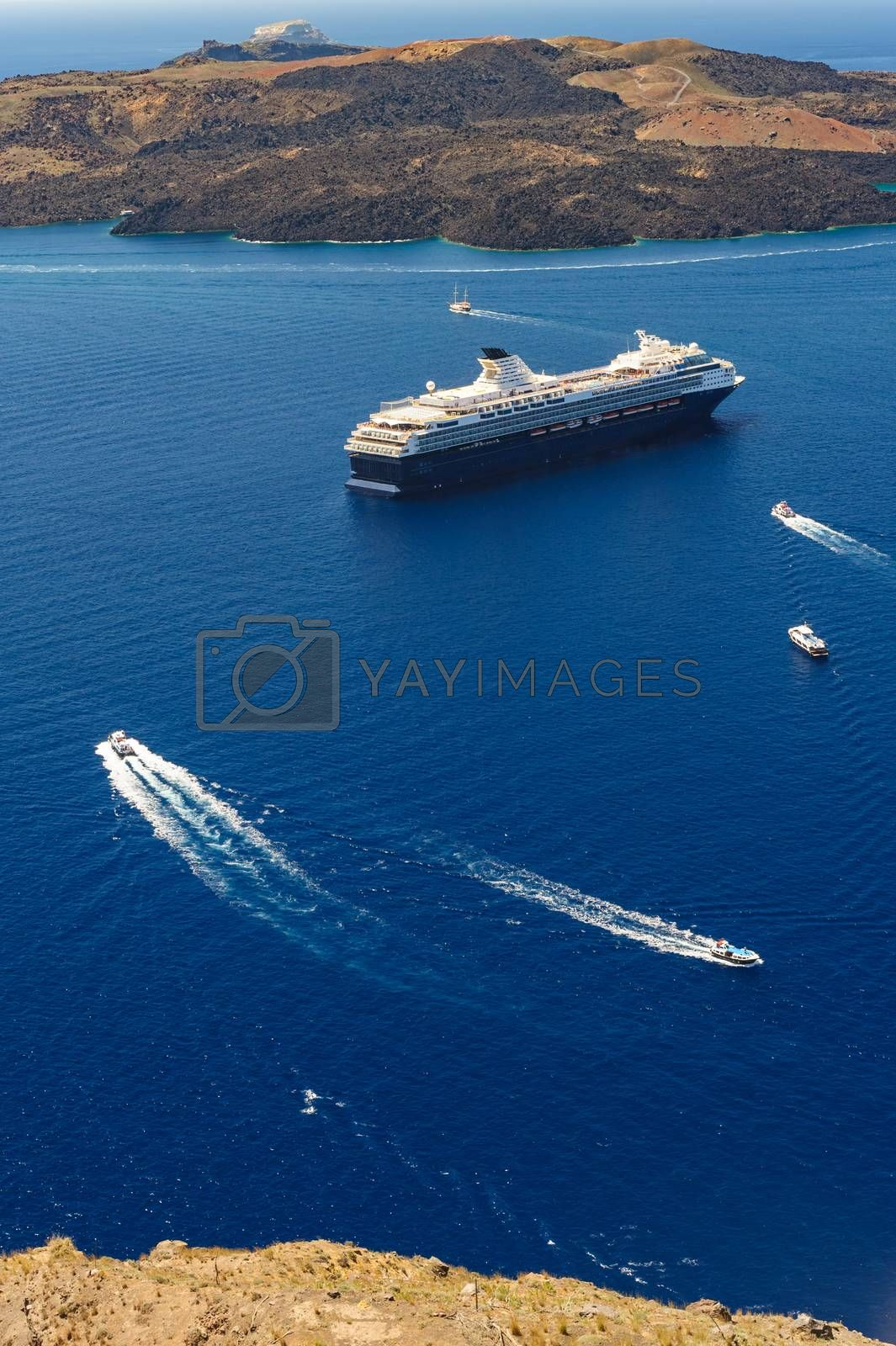 Typical view from Fira village to caldera sea with cruise ship at sunset, Santorini island, Greece