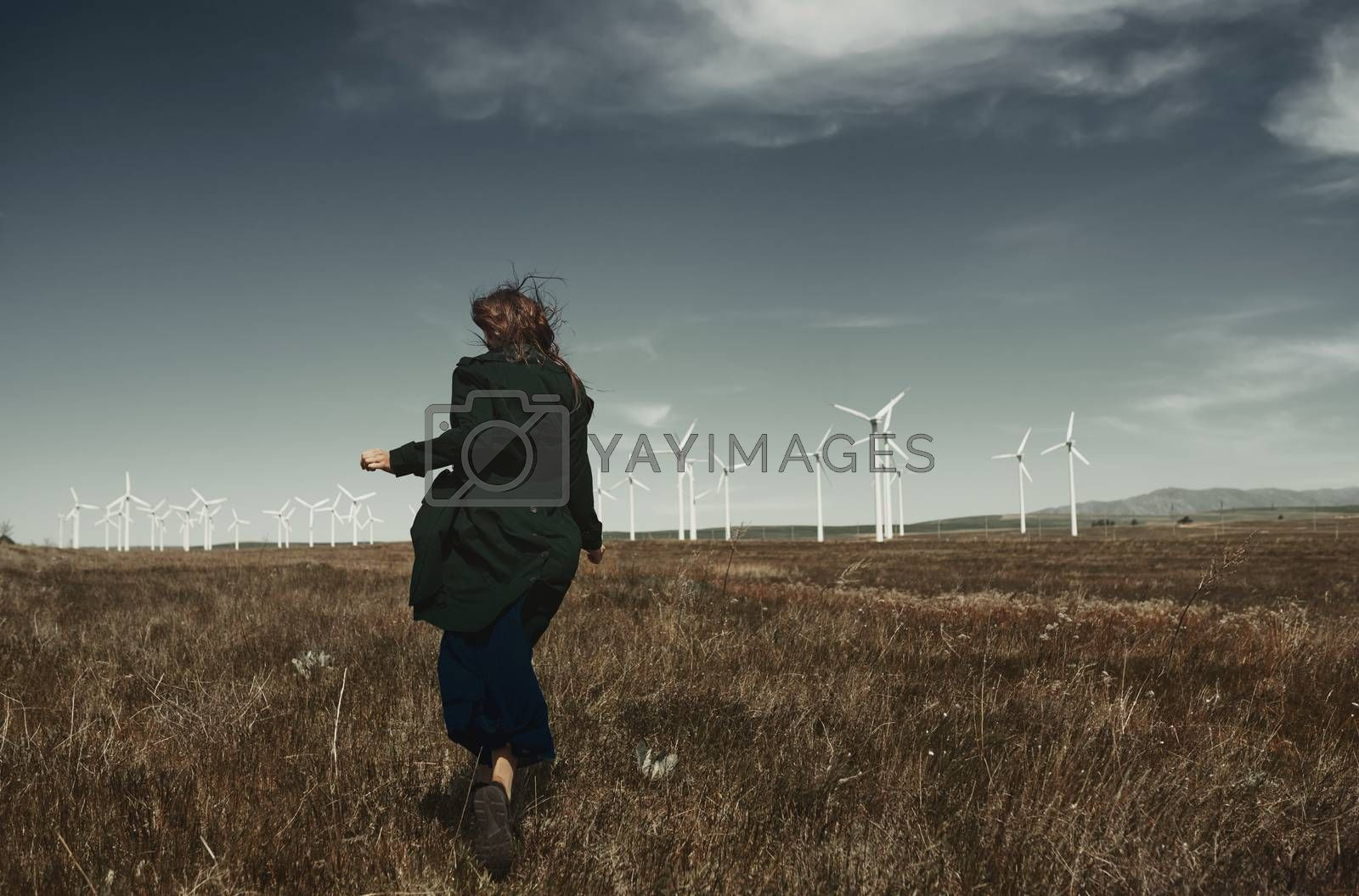 Woman with long tousled hair next to the wind turbine with the w by Novic