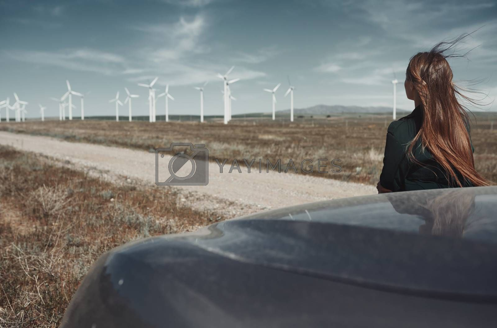 Woman leaning to her car next to the wind turbines site