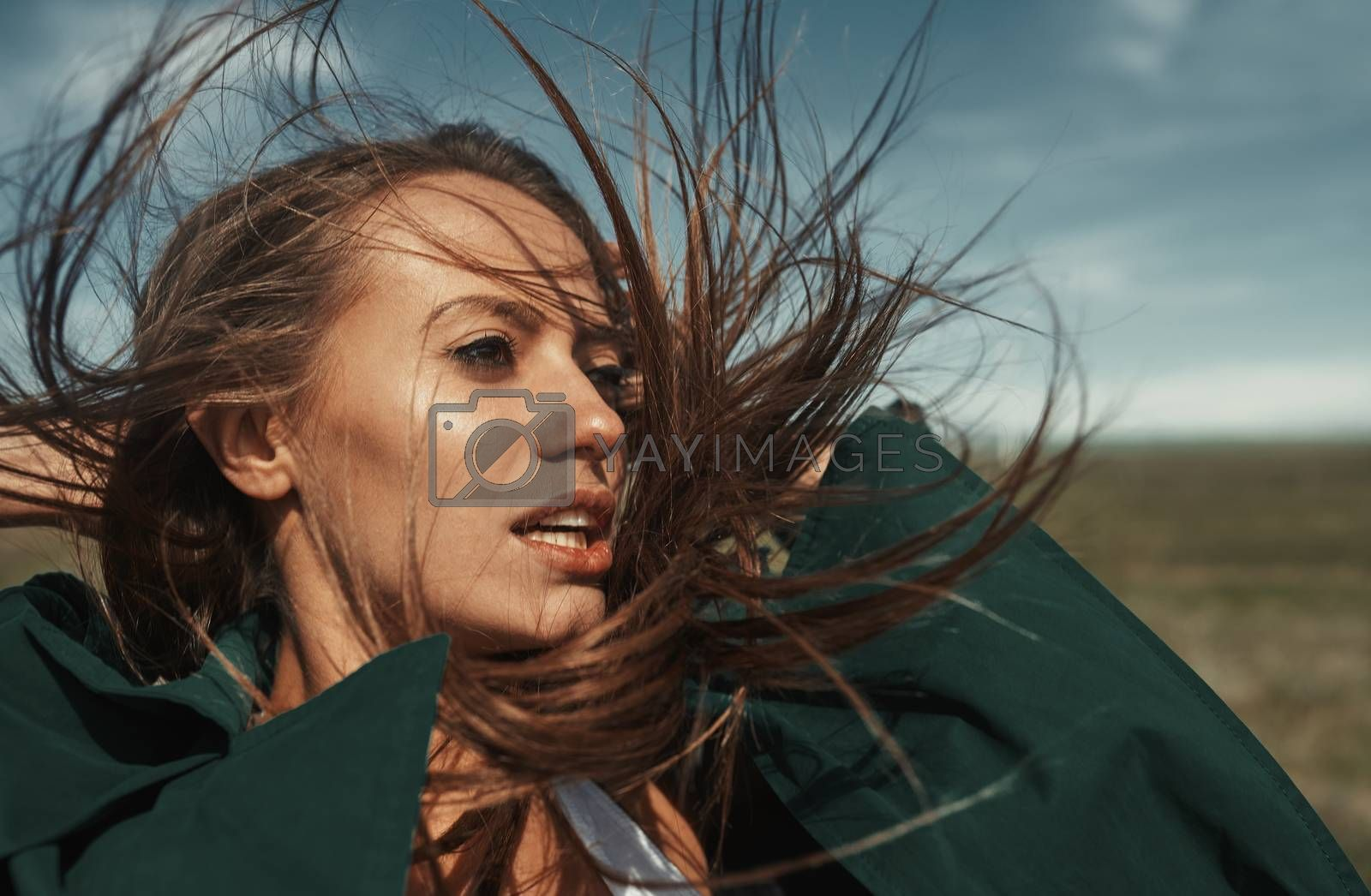 Woman outdoors with tousled wind blown hairs