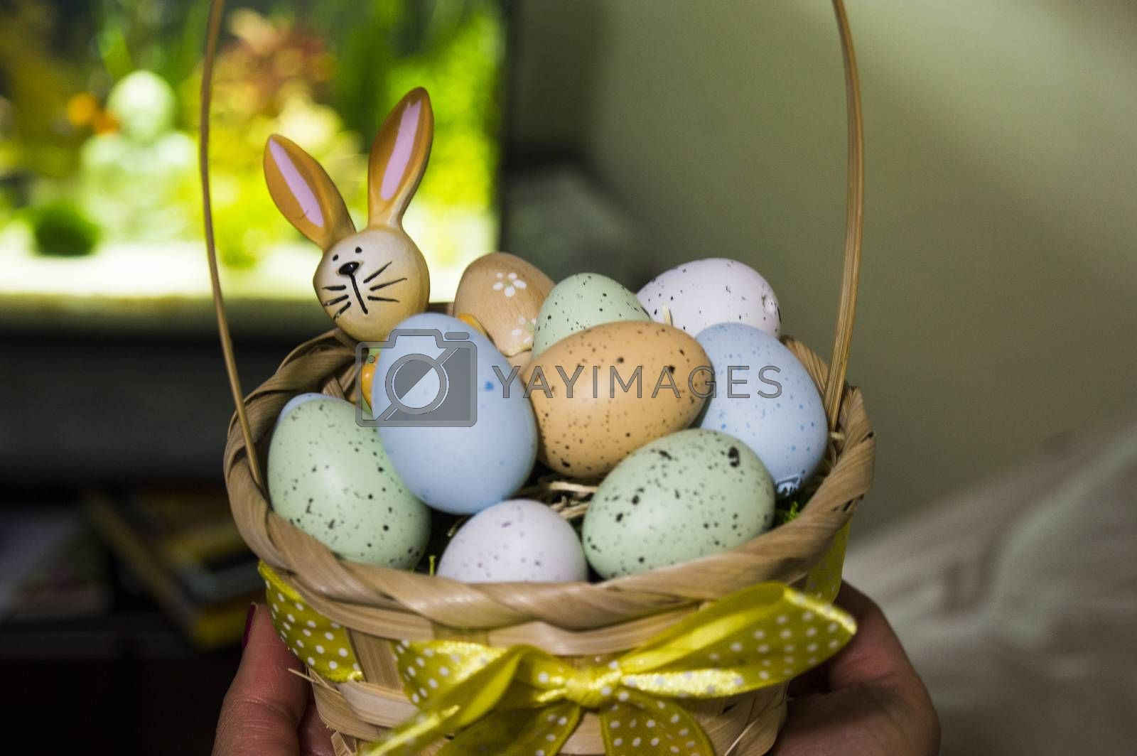 Easter bunny closeup with colorful eggs and fish aquarium in background
