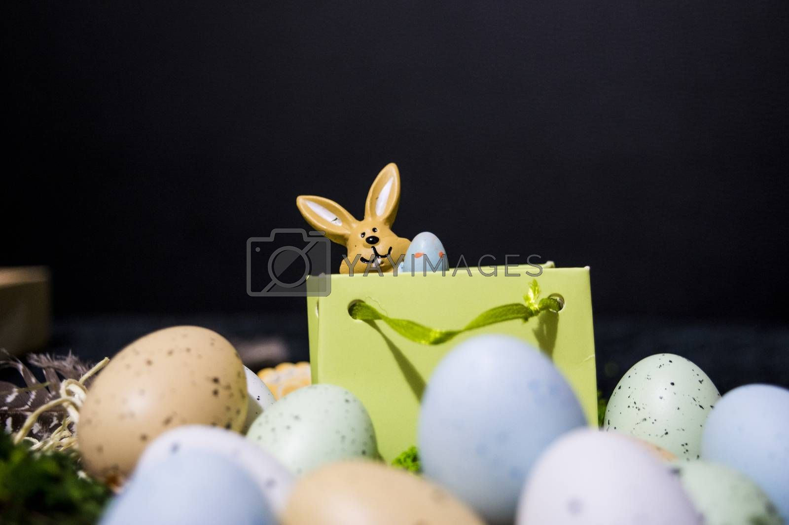 Small Easter bunny peeking from gift bag with colorful easter eggs