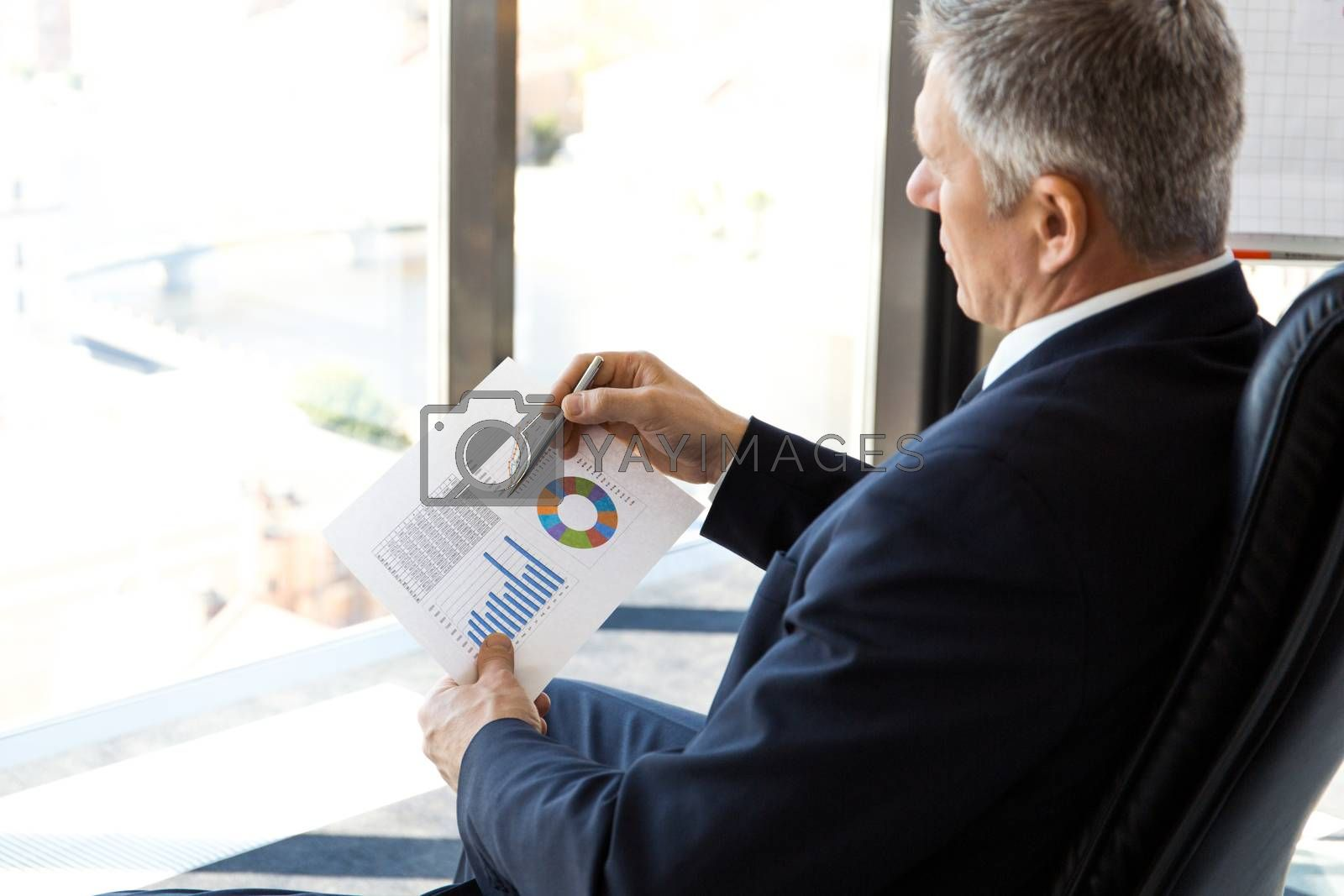 Mature businessman sitting alone in office with large panoramic windows with view at city and looking at diagrams and financial reports