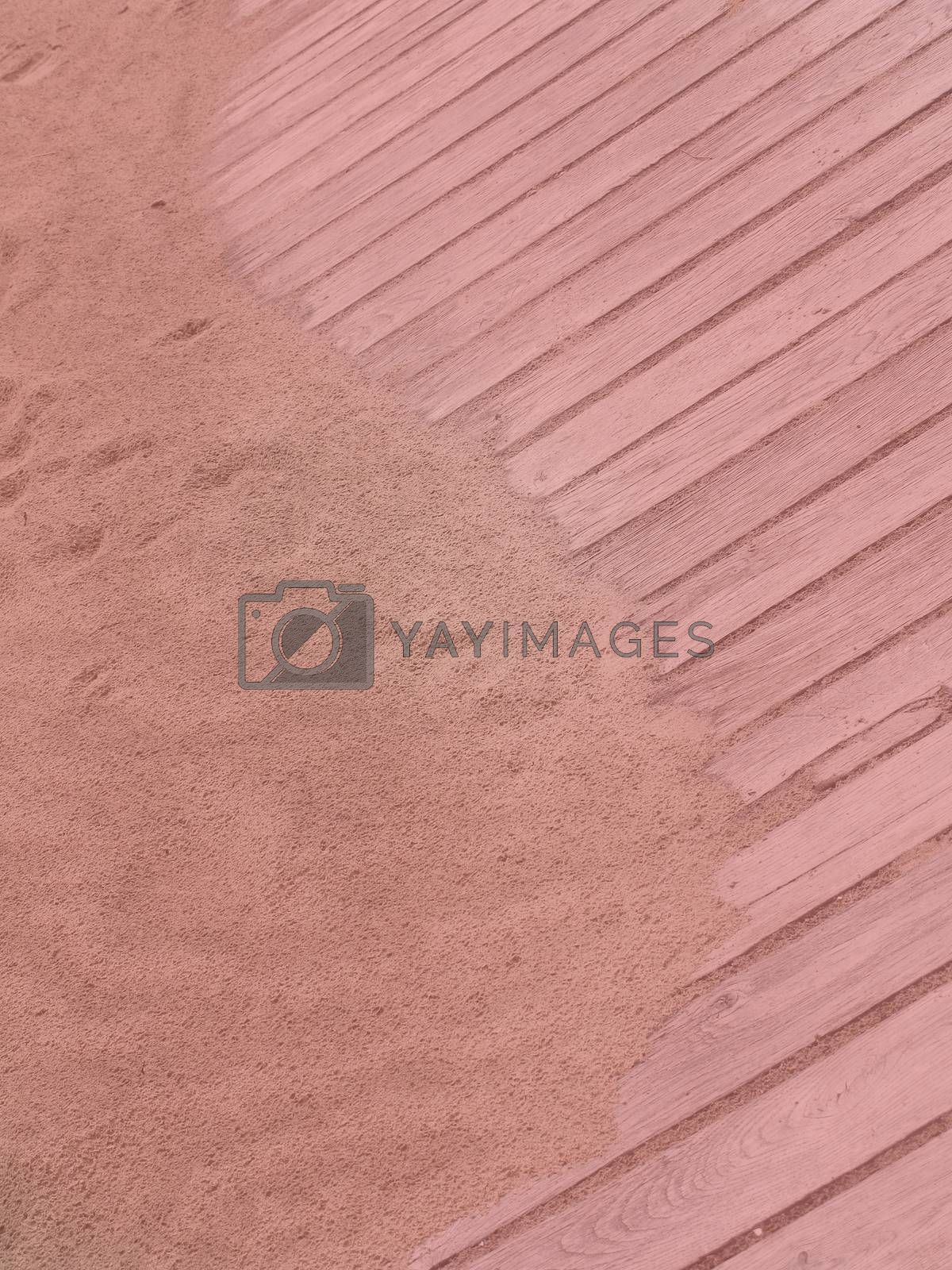 Rustic Yin Yang shape on sandy boardwalk vertical image toned in trend color Living Coral.