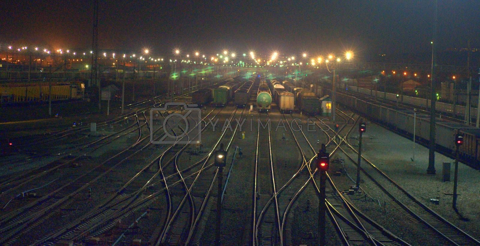 Night shooting of the crossing on the railway tracks, the bridging of the roads at the station flickers in the lights. Blur.