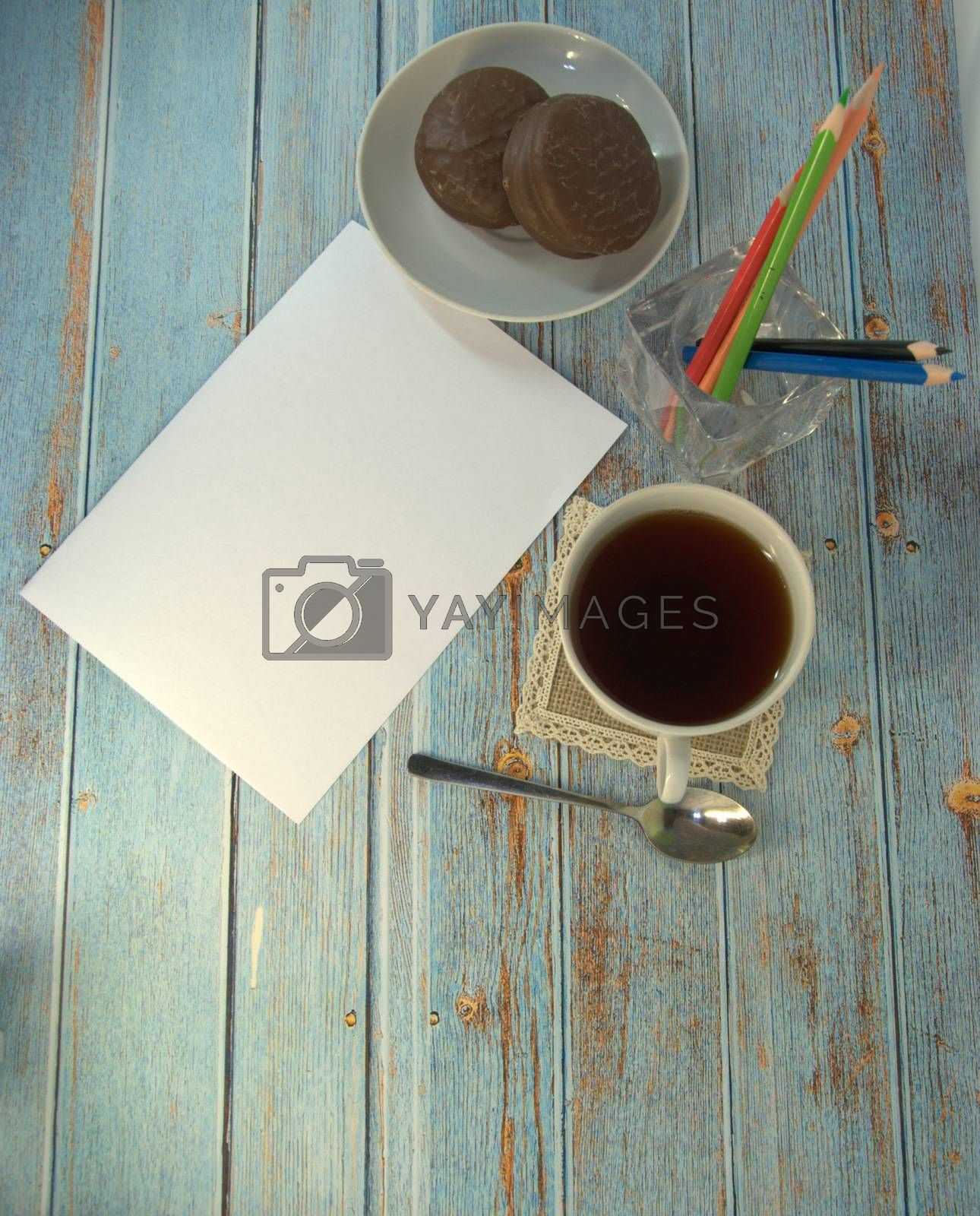 A cup of tea, spoon, teralka with chocolate cookies and pencils on a wooden table. Close-up.