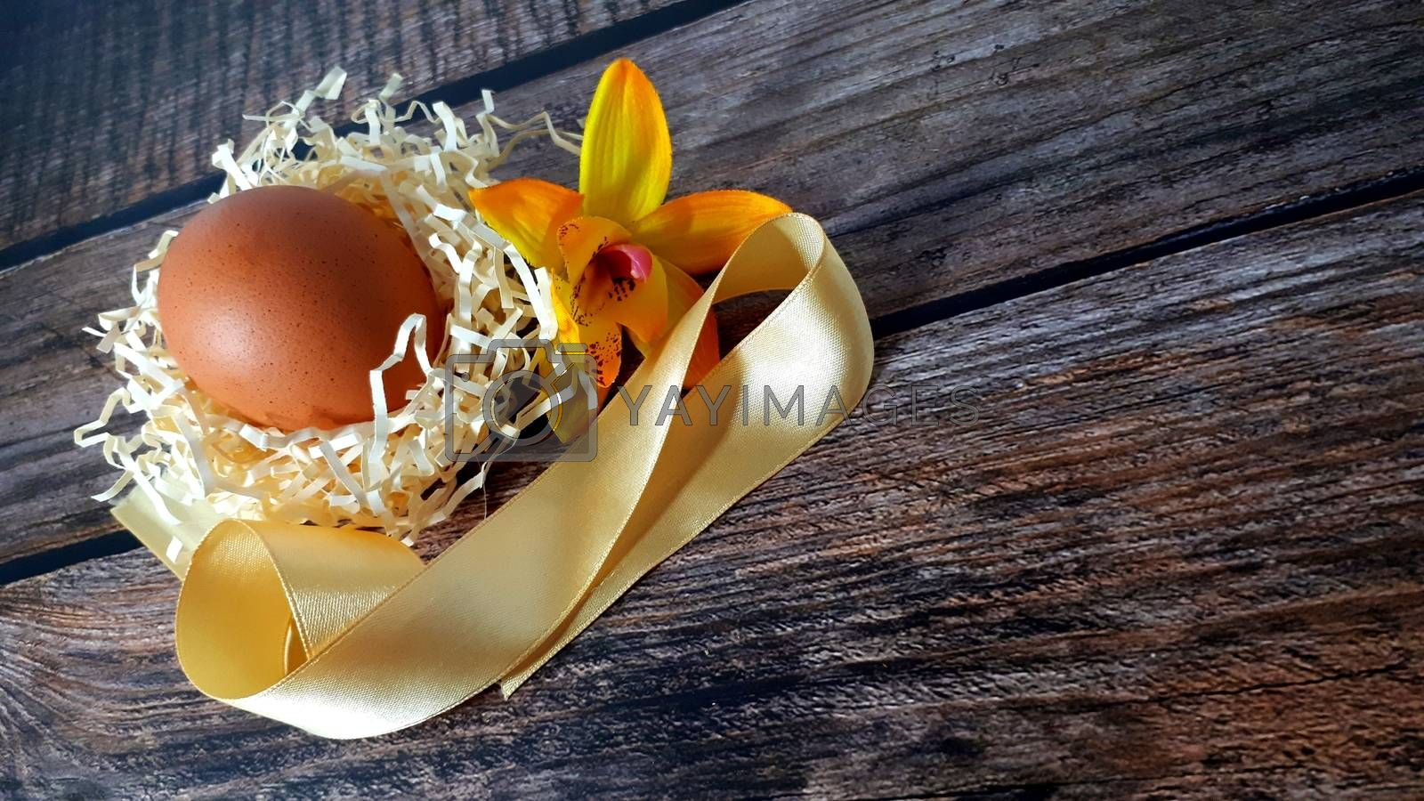 Chicken egg in a nest of straw and beige satin ribbon on a wooden table. Close-up.