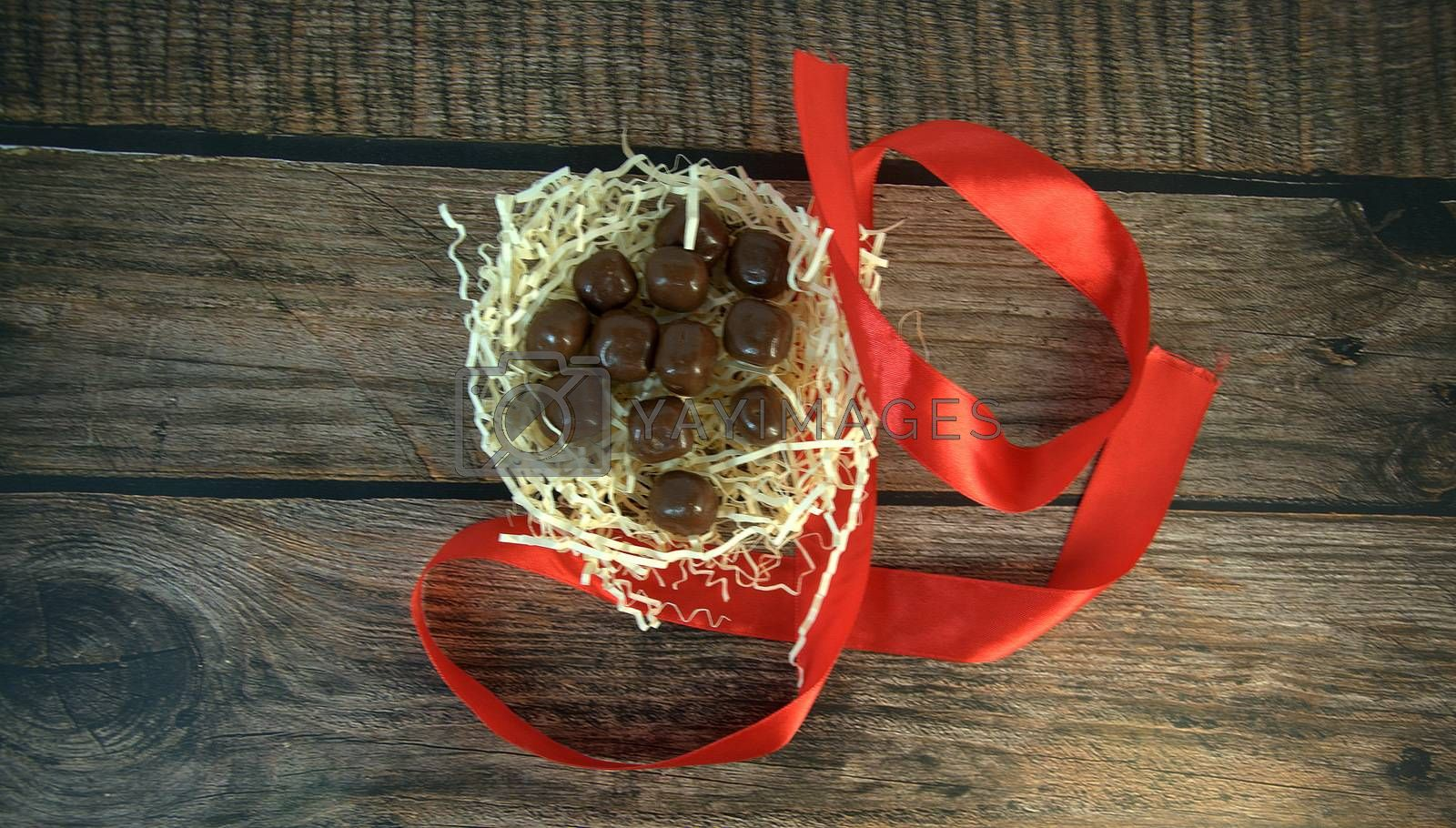 A nest of straw with chocolates and scarlet ribbon on a wooden table. Close-up.