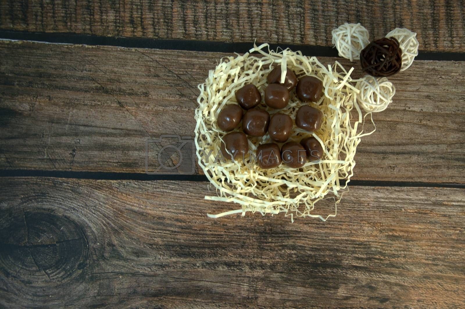 A nest of straw with chocolates and and decorative balls on a wooden table. Close-up.