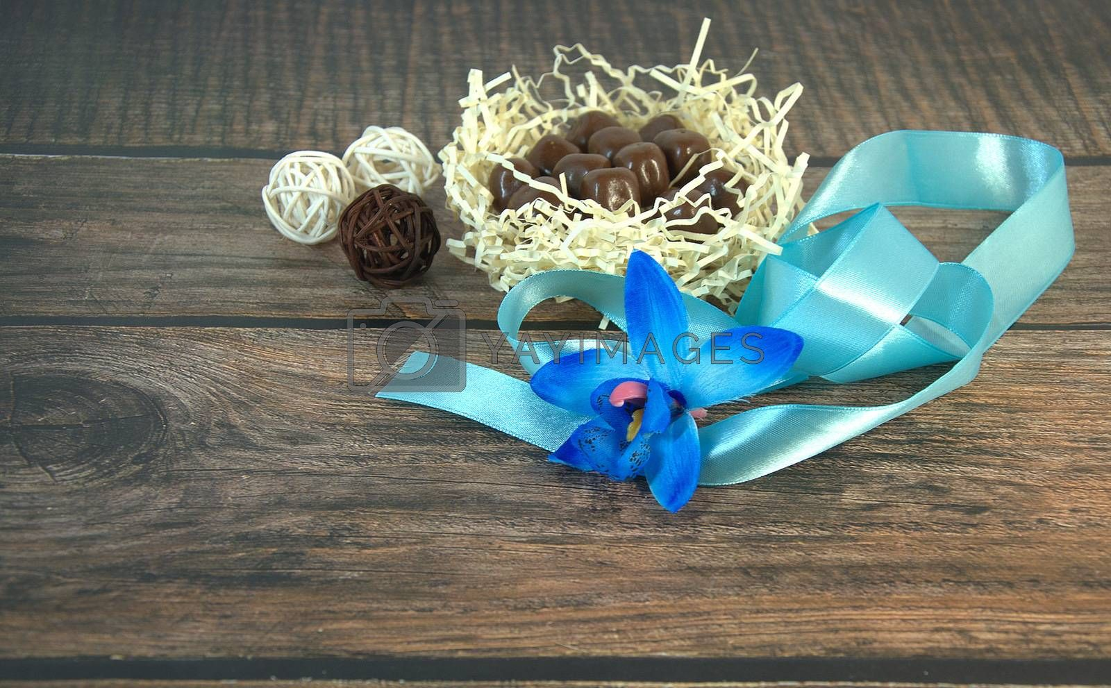 A nest of hay with chocolates, a blue ribbon, a bud of blue orchid and decorative balls on a wooden table. Close-up.