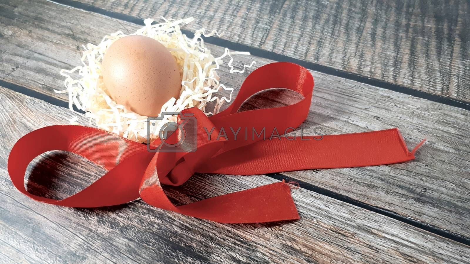 Chicken egg in a nest of straw and red satin ribbon on a wooden table. Close-up.