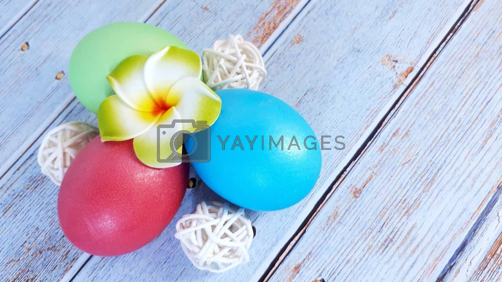 Three Easter eggs with decorative balls and a flower bud on a wooden table. Close-up.