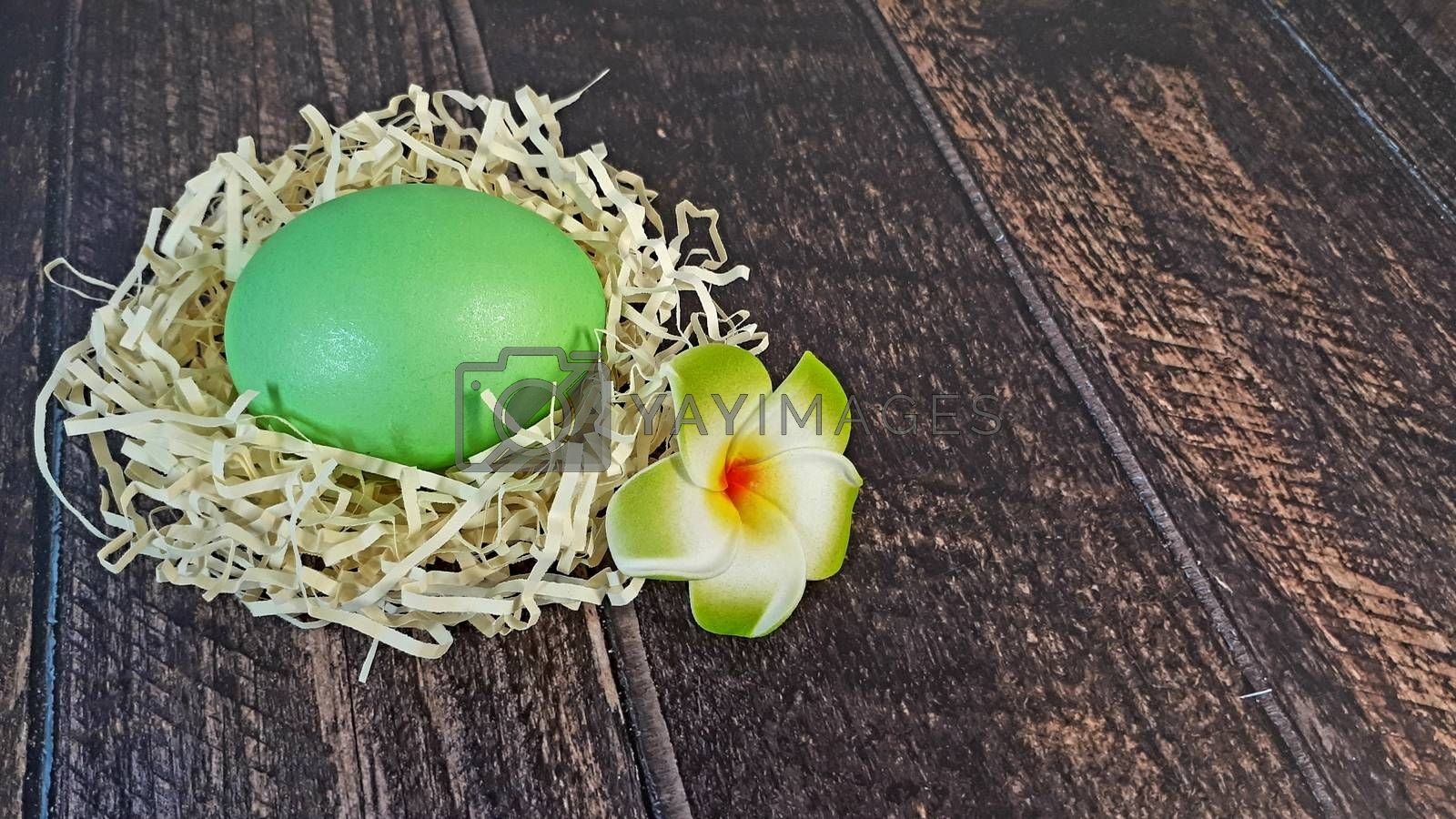 Easter egg in a nest of straw and a bud on a wooden table. Close-up.
