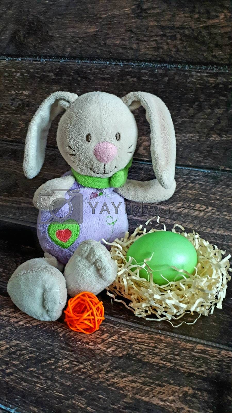 Easter bunny with egg in a nest of straw. Close-up.