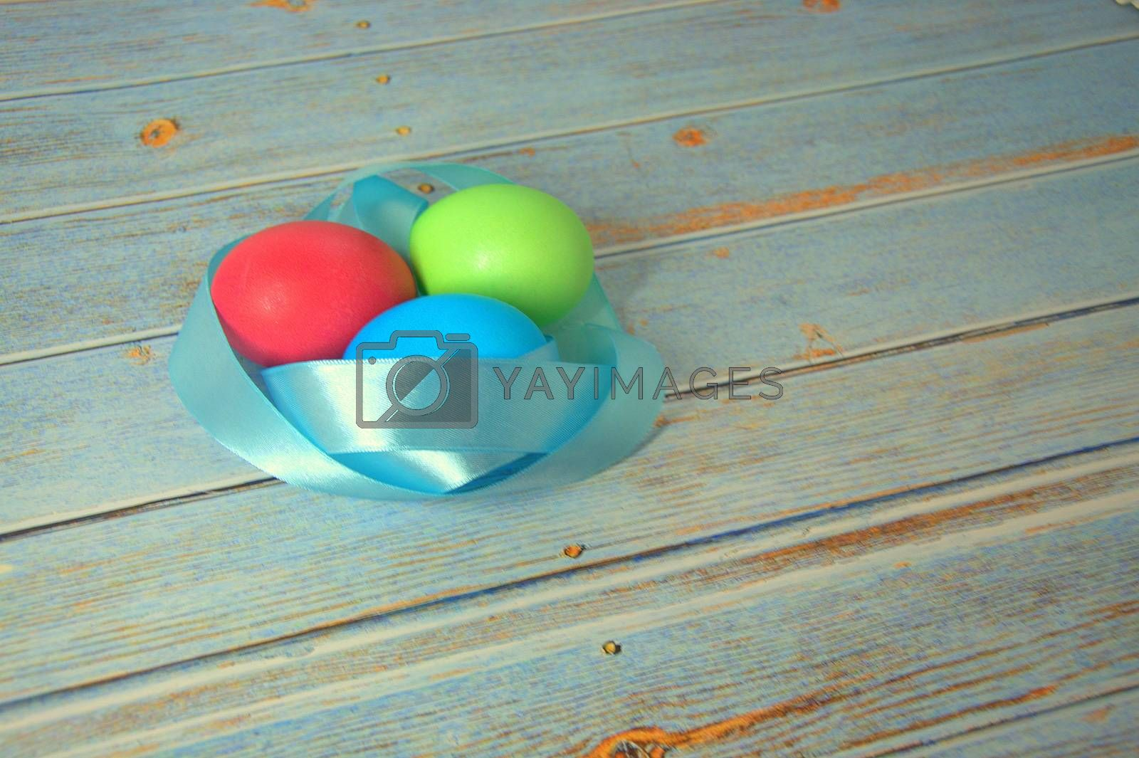 Three Easter eggs with a blue satin ribbon lie on a wooden table. Close-up.