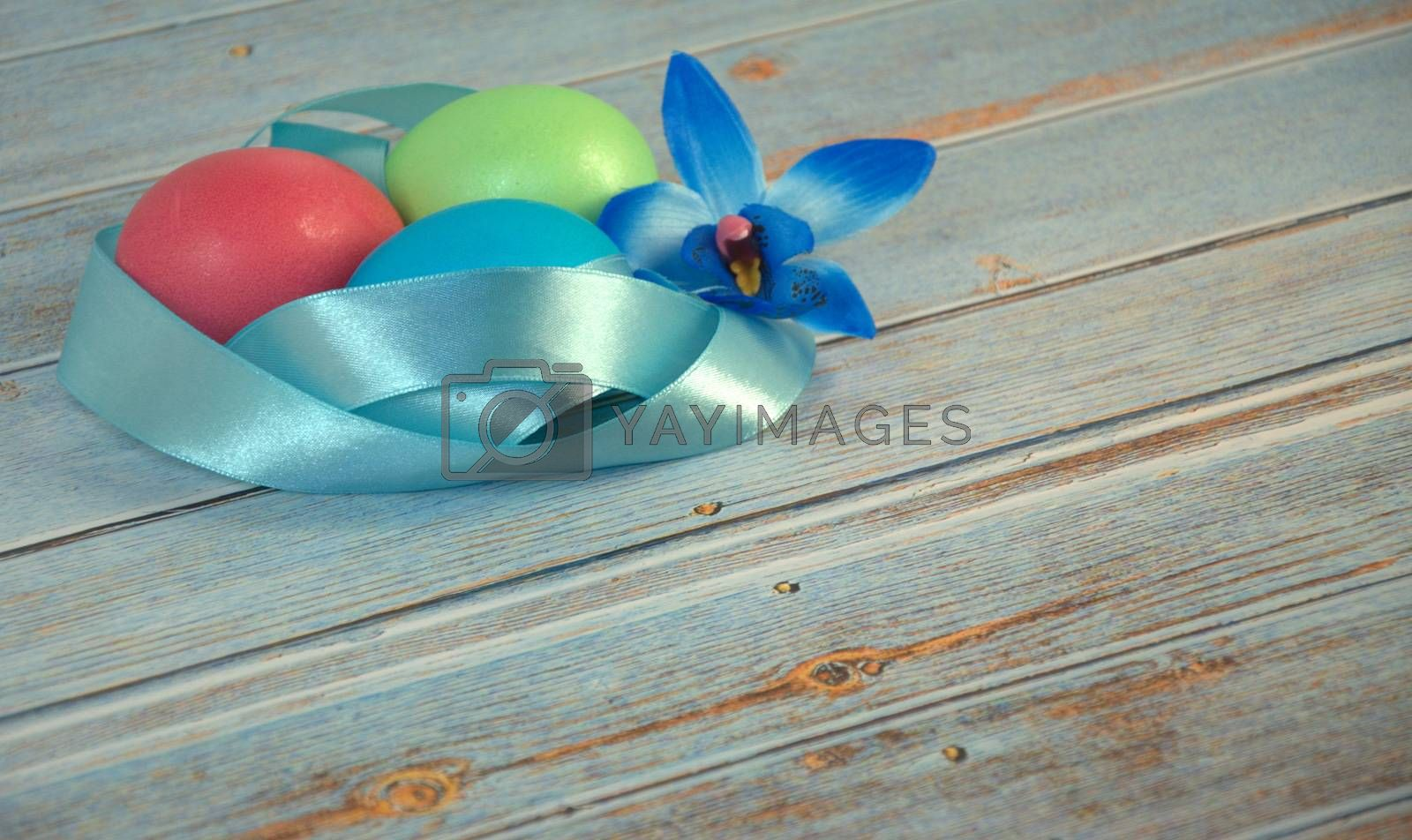 Three Easter eggs with a blue satin ribbon and an orchid bud on a wooden table. Close-up.