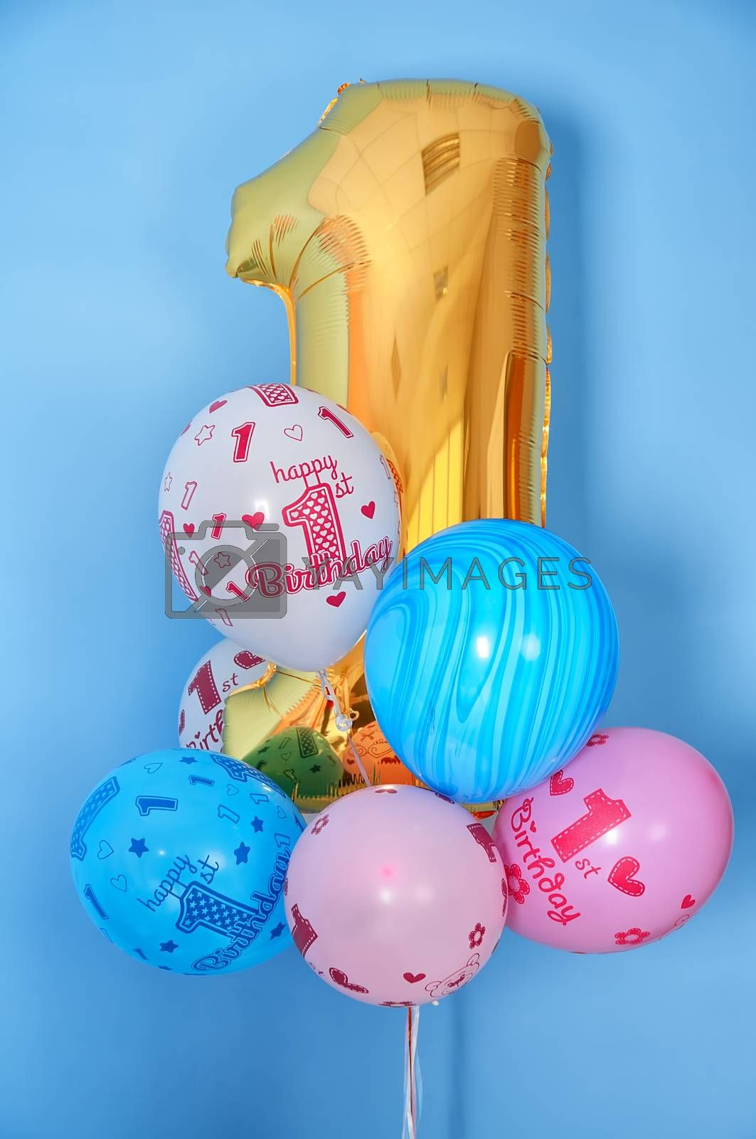 Composition for first birthday greeting with bouquet of trendy colorful pink, gold, white, blue balloons with HAPPY BIRTHDAY text and golden digit one 1 on light blue background for greeting-card