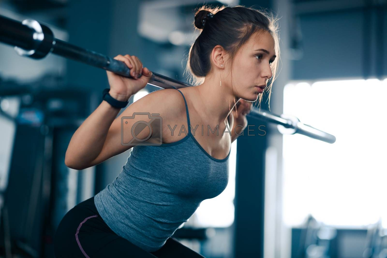 Attractive Young Sports Woman Doing Squats with Barbell in the Gym. Fitness and Healthy Lifestyle Concept.