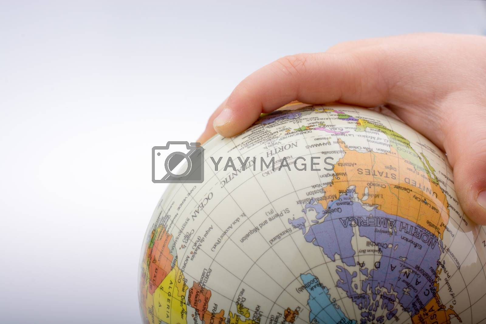 Child holding a globe in on a white background