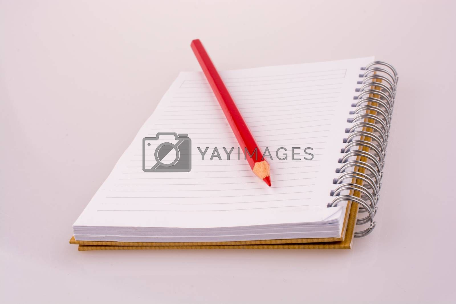 color pencil on a notebook on a white background