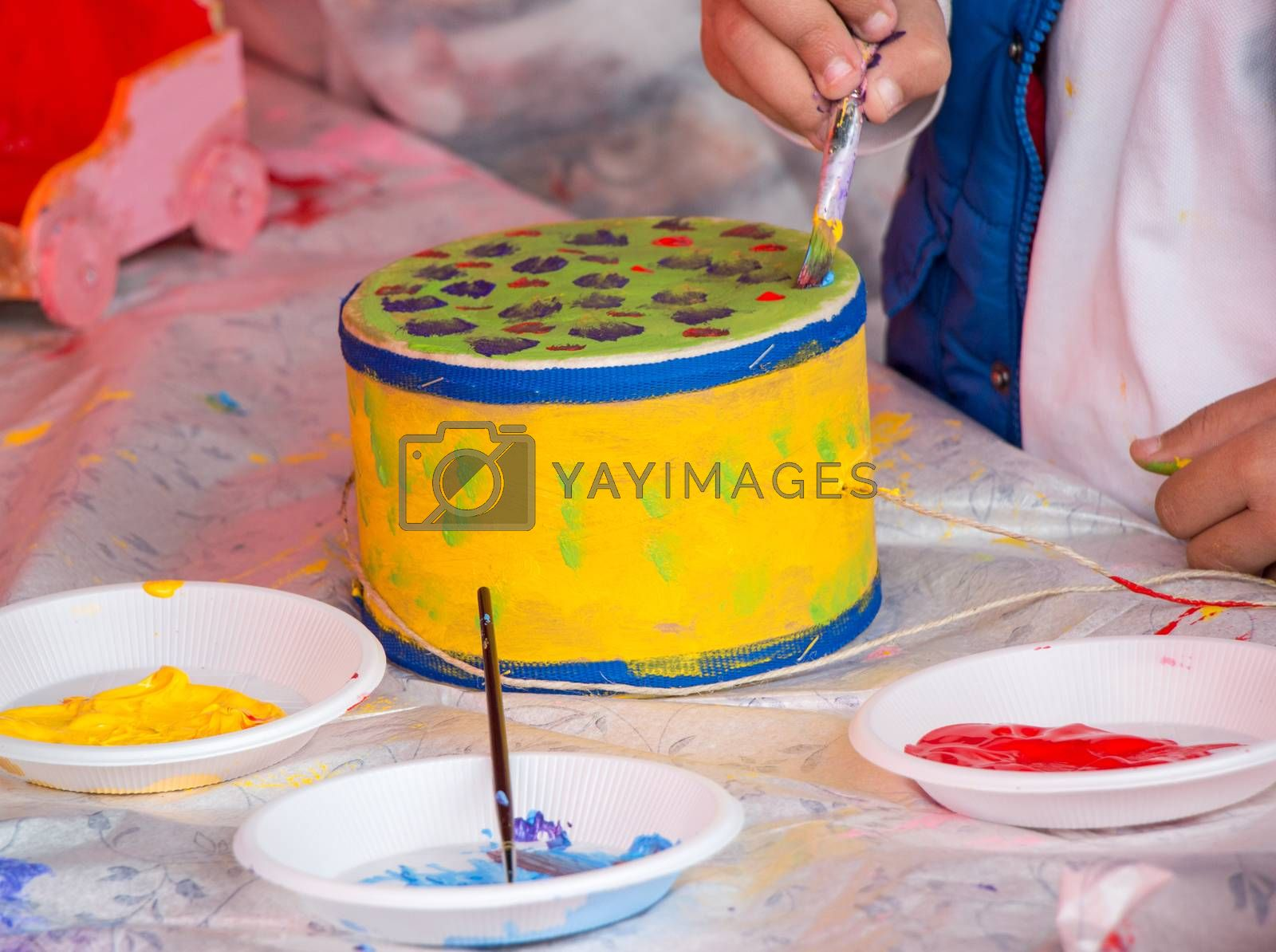 Young children decorating handmade drum