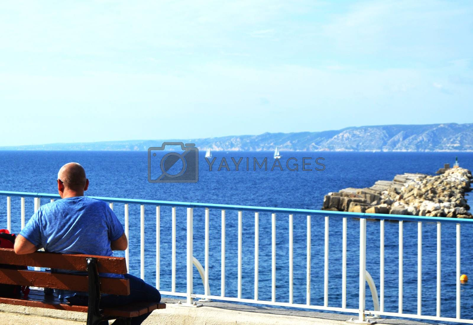 A young man traveler sitting on a bench on the Mediterranean coast on the promenade of Marseille. Back view of the beautiful sea panorama and sailboats, a COPY of the SPACE.