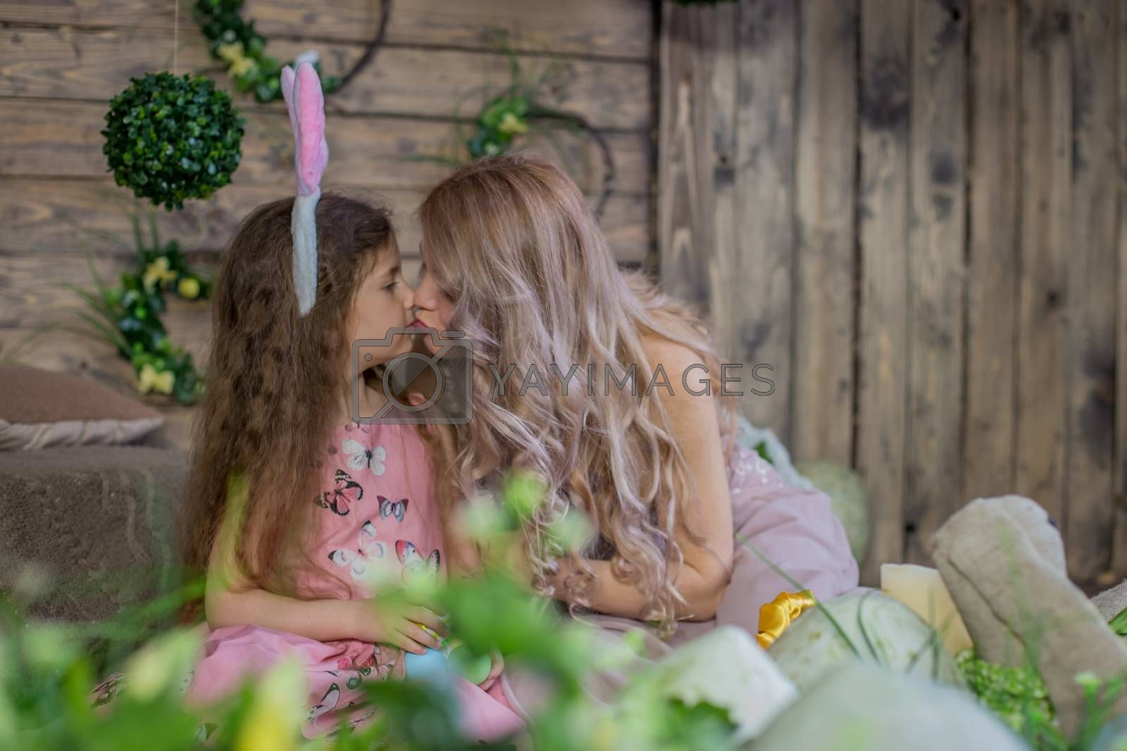 Little child girl wearing bunny ears kissing her mother among Easter decoration in studio