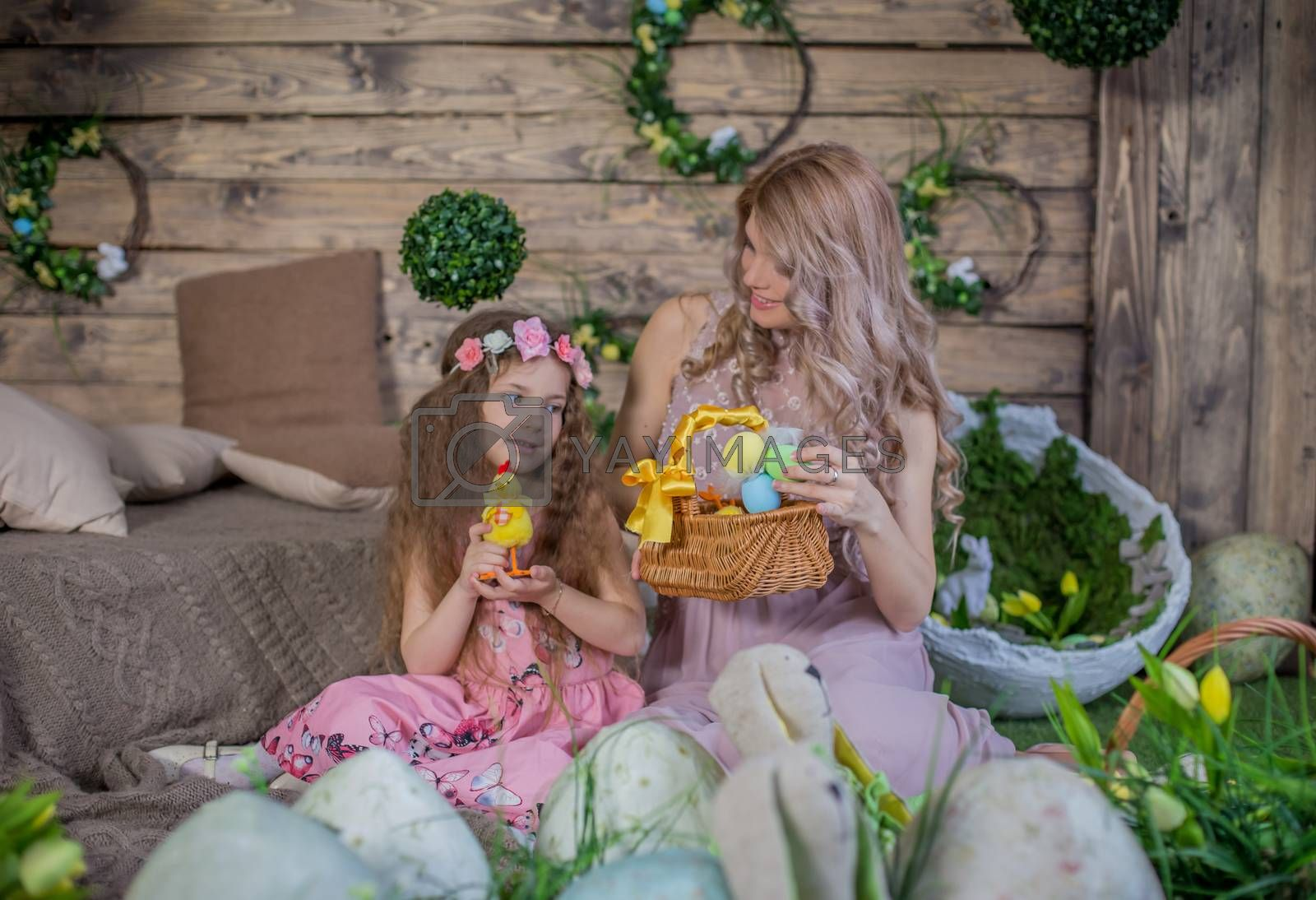 Little child girl and her mother among Easter decoration in studio
